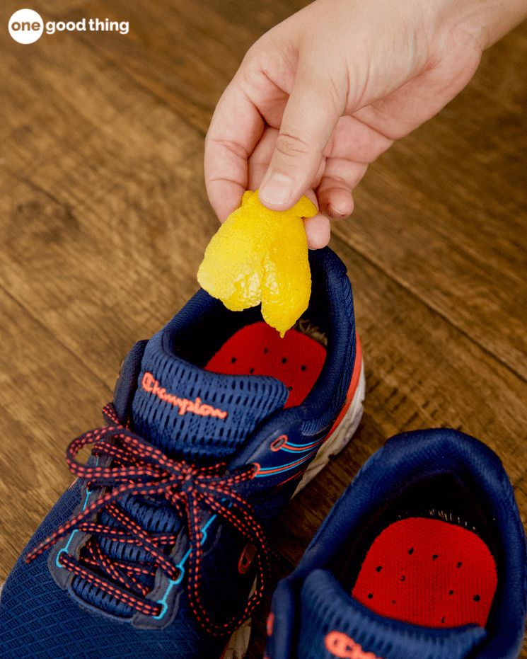 A pair of blue and red Champion athletic shoes with a lemon peel being placed inside
