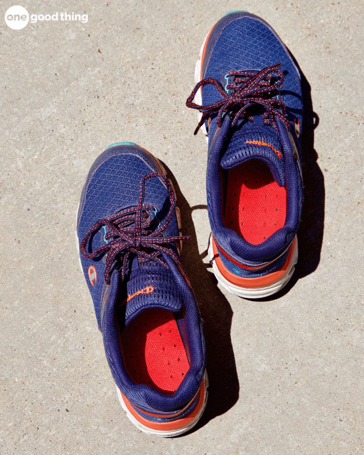 A pair of blue running shoes with red insoles outside on the ground in the sunshine