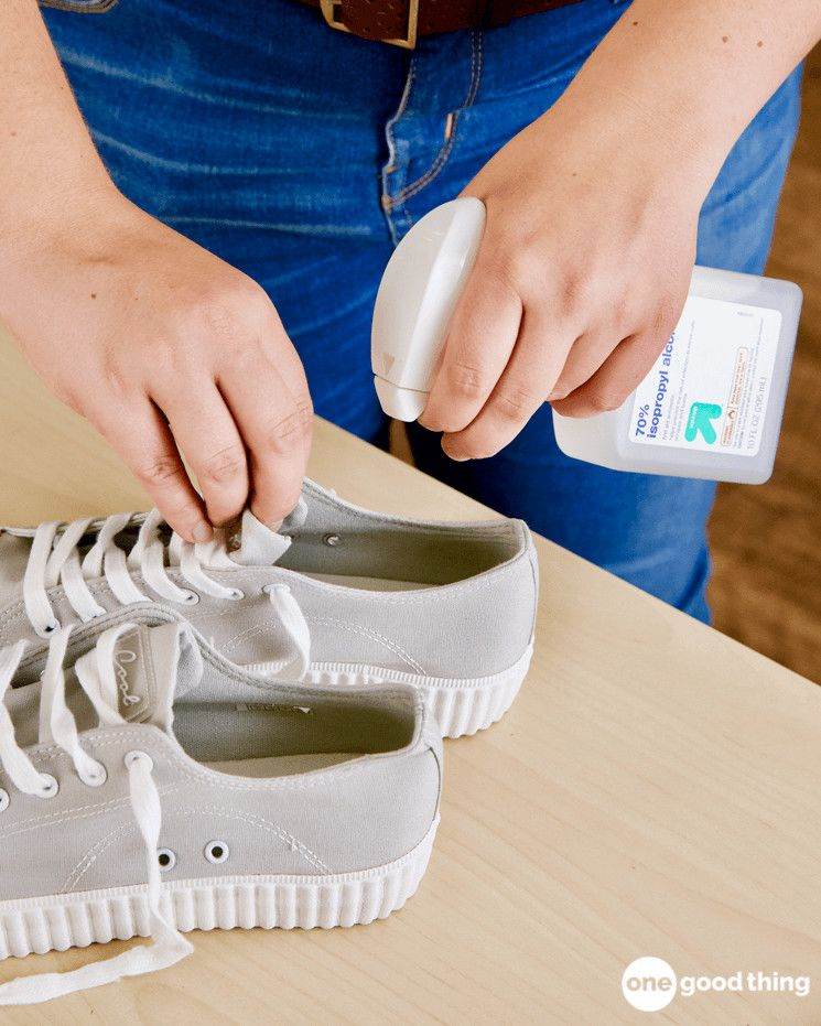 A person spraying 70% isopropyl alcohol into a pair of grey canvas low-top shoes to neutralize odor