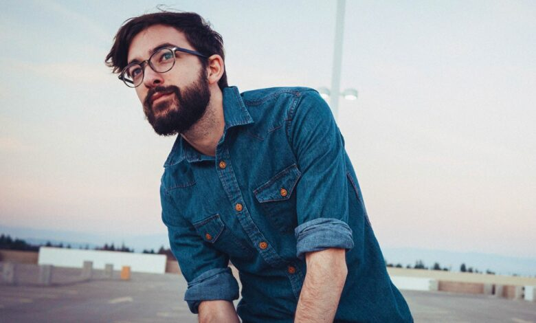 Bearded man wearing glasses and blue flannel