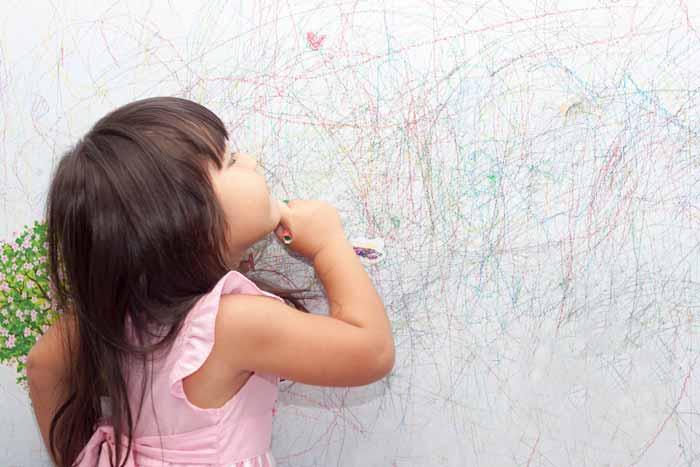 کودک خوشکل در حال نقاشی روی دیوار با مداد رنگی