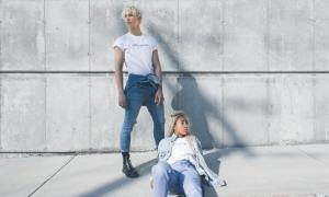 Man and woman in white t-shirt and blue jeans against simple grey concrete wall